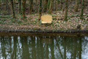 Entsorgte alte Sitzbank am Ufer eines Bachs.