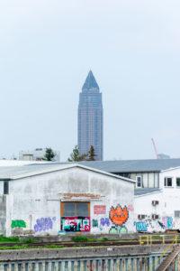 Deutschland, Hessen, Frankfurt, der Messturm hinter einer Gewerbehalle am Main.