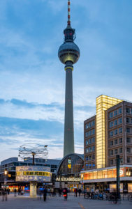 World time clock, train station and Berolina House on Alexanderplatz, in the back television tower, Mitte, Berlin