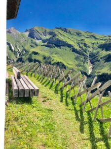 Wanderweg, Bank, Sitzbank, Holz, Hochformat, Zaun, Latten, Wiese, Himmel, Blau, Grün, Alpen, Berge, Wanderung, Friede,, Ruhe, Gelassenheit,