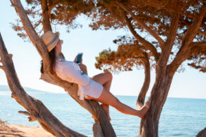 Mädchen mit Smartphone auf einem Baum am Strand