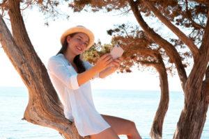 Mädchen mit Smartphone auf einem Baum am Strand, lächeln, Selfie