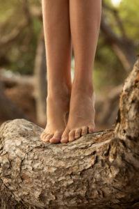 Teenage girl on tiptoe on a tree, detail, feet