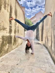 Handstand einhändig, junge Frau, Altstadt, Gassen, blauer Himmel, Steinboden, Sommer, Lebensfreude, Stärke, Urlaub, verrückt, über Kopf,