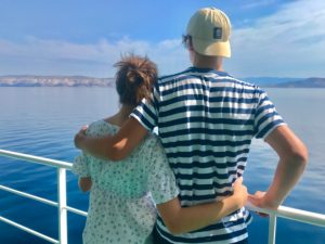 Looking into the distance, coast, ship, sea, railing, hugging, rear view, siblings, young woman and man, sun, summer, ferry, vacation, longing, morning light