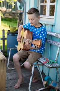Boy playing guitar in front of garden house