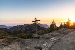 Signpost at the 'Roque Nublo' monolith plateau in the high mountains of Gran Canaria (1813 m altitude) at sunset, Spain