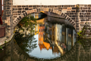 Reflection of house facades under the Henker's Bridge in the evening light, Nuremberg city center, Franconia, Bavaria, Germany