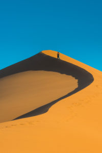 Woman hiking up the  giant sand Dune 45, Namib-Naukluft National Park, Namibia
