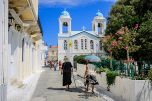 Andros town, Andros island, Cyclades, Greece - Locals and tourists walk through the narrow, colorful streets of the old town of the capital Andros (Chora).