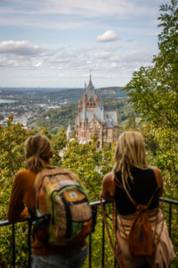 Koenigswinter, North Rhine-Westphalia, Germany - Drachenburg Castle on the Drachenfels, attraction and excursion destination in the Siebengebirge on the Rhine, young tourists with dreadlocks at the viewpoint in front of the northern Rhine Valley.