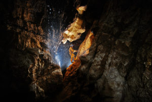 Cave explorer in dripping water of a cave