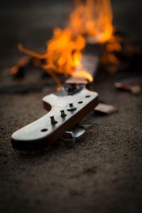 brennende Gitarre liegt auf dem Boden