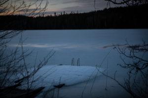 zugefrorener See, eingeschneiter Holzsteg, Dämmerung