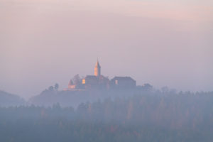 Sunrise over the Leuchtenburg with fog over the Saale valley.