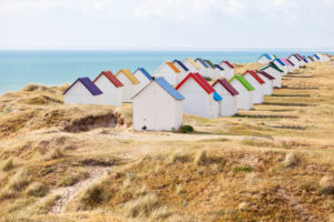 Eve mood at the colorful beach huts of Gouville on the Norman coast.