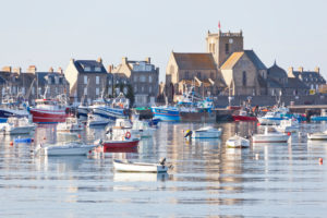 Boats in the harbor at Barfleur, with the Church of St. Nicolas behind. The town is one of the most beautiful places in France.