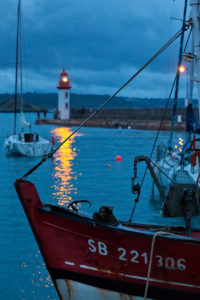 In the evening at the lighthouse of Eruqy - harbor entrance with boats. Brittany, France