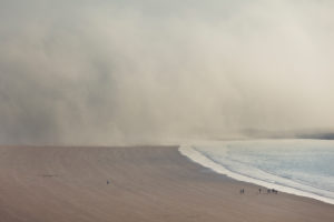 Tidal fog moves over the beach at Eruy. A small group of people (right) shows the proportions. Erquy, Brittany, France