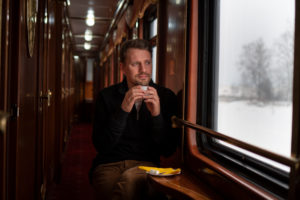 Trans-Siberian railway in winter, man sitting in train looking out of window, Russia