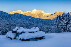 Snowy bench on Buckelwiesen (meadow) in Mittenwald