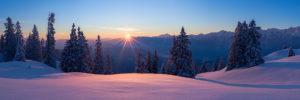 Sonnenaufgang auf der Wallgauer Alm mit Blick auf das Karwendelgebirge, im Vordergrund glitzert der Pulverschnee in der aufgehenden Sonne,