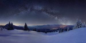 Milchstraße über dem Karwendel, im Vordergrund die verschneite Almwiese der Wallgauer Alm mit Pulverschnee auf den Bäumen, ie beleuchteten Orte sind Krün und Mittenwald, Berge: Simetsberg, Benediktenwand, Karwendelgebirge, Arnspitze