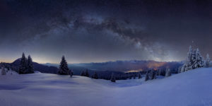 Milky way above the Karwendel, in the foreground the snowy alpine meadow of the Wallgau Alm with powder snow on the trees, the illuminated places are Krün and Mittenwald, mountains: Simetsberg, Benediktenwand, Karwendel mountains, Arnspitze