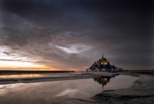 Le Mont-Saint-Michel in der Normandie bei Sonnenuntergang und dramatischem Himmel