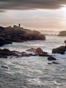 Pink Granite Coast with impressive pink granite rocks and Phare de Ploumanach lighthouse in the evening, contre-jour