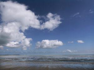 Küste bei Ebbe, blauem Himmel und Wolken. Bretagne bei St. Malo