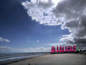 Eine Gruppe Strandsegler wartet auf den Einsatz. Die Sonne lässt die Segel erstrahlen