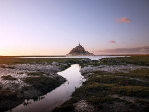 Le Mont-Saint-Michel bei Sonnenuntergang. Nach der Flut zieht sich das Wasser zurück