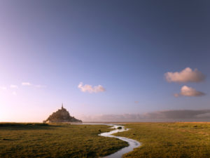 Le Mont-Saint-Michel at sunset. A small stream meanders towards the Klosterberg