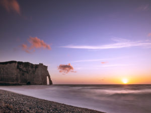 The Porte D'Aval rock gate near Étretat at sunset