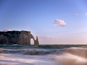 The Porte D'Aval and Aiguille rock gates at Étretat. The surf and cliffs are illuminated by the evening sun