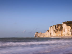 The cliffs of Étretat glow in the evening sun. View from the beach to the Porte D'Amont rock gate