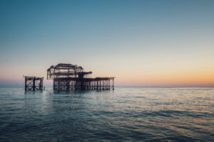 Abgebranntes West Pier am Meer bei Dämmerung, Brighton, England