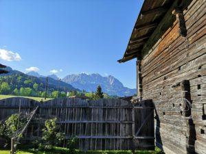 Blick auf den Wilden Kaiser mit Holzscheune und Zaun im Vordergrund