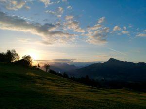 Blick aufs Kitzbüheler Horn bei Sonnenaufgang mit bauernhof im Vordergrund.