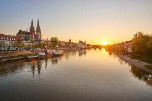 Regensburg Cathedral and Stone Bridge at sunset over the Danube from the Marc Aurel Ufer, Regensburg, Bavaria, Germany