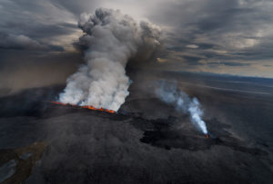 Lava and plumes from the Holuhraun Fissure by the Bardarbunga Volcano, Iceland. Sept. 1, 2014Aerial view of the eruption at the Holuhraun Fissure by the Bardarbunga Volcano, Iceland. Looking South East with the Kverkfjoll mountain range in the distance. Dust storms result from the Hurricane Cristobal in the South Atlantic. On August 29, 2014, a fissure eruption started in Holuhraun at the northern end of a magma intrusion that had moved progressively north, from the Bardarbunga volcano. Bardarbunga is a stratovolcano located under Vatnajokull, Icelands most extensive glacier.