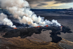 Lava and plumes from the Holuhraun Fissure by the  Bardarbunga Volcano, Iceland. Sept. 1, 2014  Aerial view of the eruption at the Holuhraun Fissure by the Bardarbunga Volcano, Iceland. Looking South East with the Kverkfjoll mountain range in the distance. Dust storms result from the Hurricane Cristobal in the South Atlantic. On August 29, 2014, a fissure eruption started in Holuhraun at the northern end of a magma intrusion that had moved progressively north, from the Bardarbunga volcano. Bardarbunga is a stratovolcano located under Vatnajokull, Icelands most extensive glacier.