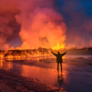 Woman standing by glowing lava. August 29, 2014, a fissure eruption started in Holuhraun at the northern end of a magma intrusion, which had moved progressively north, from the Bardarbunga volcano. Bardarbunga is a stratovolcano located under Vatnajokull, Icelands most extensive glacier. Picture date- Sept 2, 2014