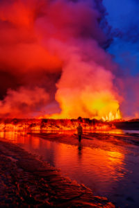 Woman watching the lava flow at the Holuhraun Fissure eruption near Bardarbunga Volcano, Iceland August 29, 2014, a fissure eruption started in Holuhraun at the northern end of a magma intrusion that had moved progressively north, from the Bardarbunga volcano.. Bardarbunga is a stratovolcano located under Vatnajokull, Icelands most extensive glacier. Picture Date-Sept 2, 2014