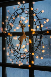 Christmas lights hanging on window indoors.