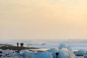 Photographers taking pictures at the Breidamerkurfjara beach, Vatnajokull Ice Cap, Iceland. Large chucks of ice calve off of the Breidamerkurjokull and then wash ashore on the black sand beach.