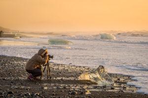 Photographer taking pictures at the Breidamerkurfjara beach, Vatnajokull Ice Cap, Iceland. Large chucks of ice calve off of the Breidamerkurjokull and then wash ashore on the black sand beach.
