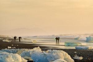 Photographers taking pictures at the Breidamerkurfjara beach, Vatnajokull Ice Cap, Iceland. Large chucks of ice calve off of the Breidamerkurjokull and wash ashore on the black sand beach.