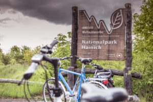 series - cycling tour, bicycles park in front of national park sign